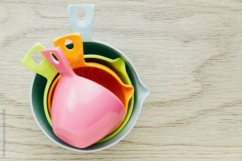 Brightly coloured measuring cups for baking by Kirsty Begg for Stocksy United