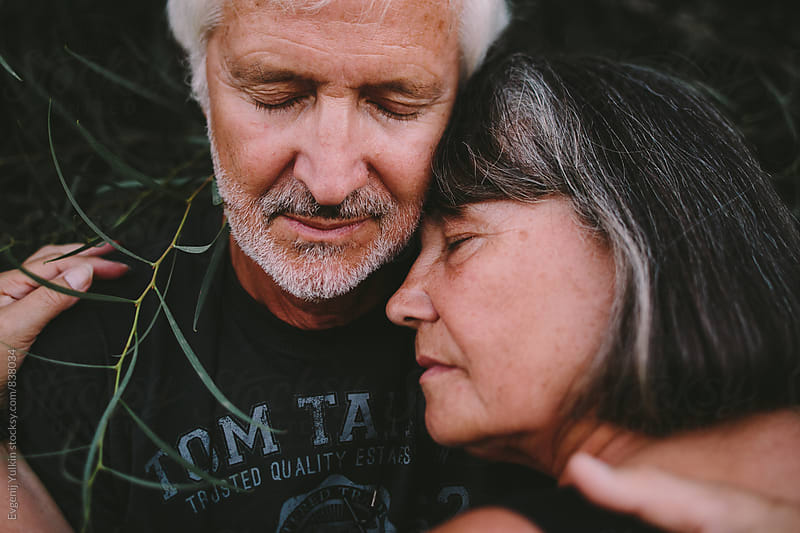 Closeup of оld couple embracing in the branches by Evgenij Yulkin for Stocksy United