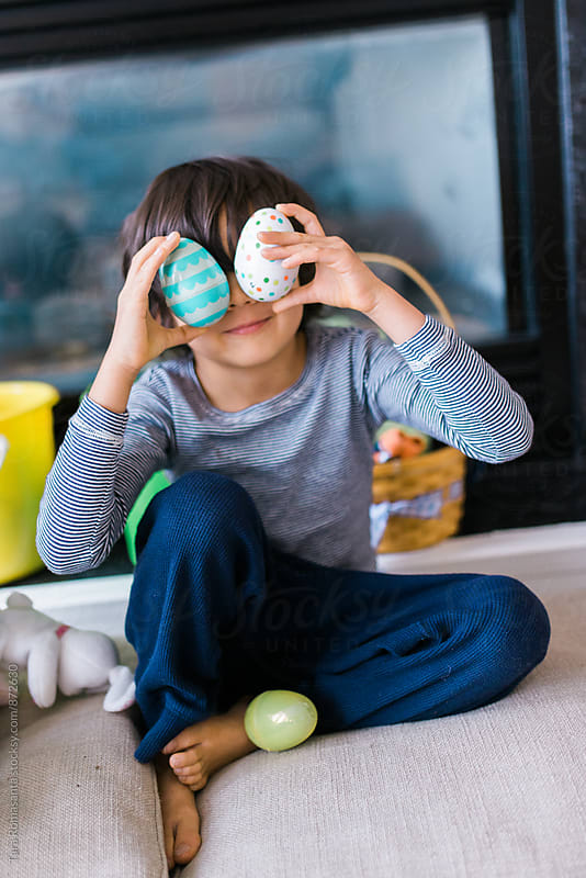 child holds decorative easter eggs over his eyes by Tara Romasanta for Stocksy United