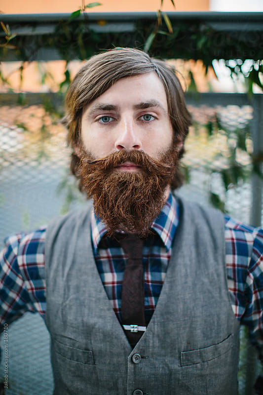 Portrait of a trendy and hip bearded man in an urban setting by Jakob for Stocksy United