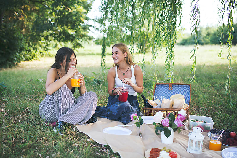 Female friends in the park having picnic on a sunny day by Jovana Rikalo for Stocksy United