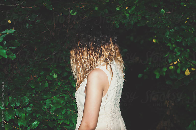 A young woman standing in front of a forest at night by Chelsea Victoria for Stocksy United