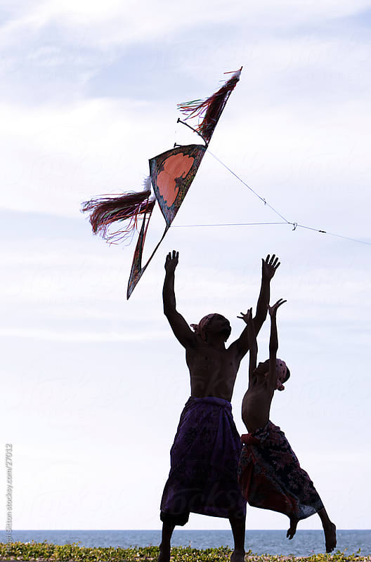 Father and Son flying traditional Malaysian kite. by Hugh Sitton for Stocksy United
