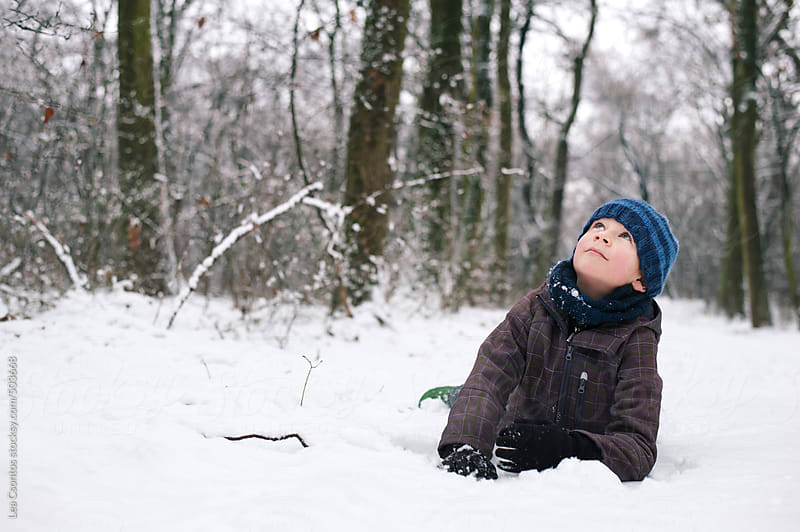 Boy lying in the snow looking up curiously to the sky. by Lea Csontos for Stocksy United