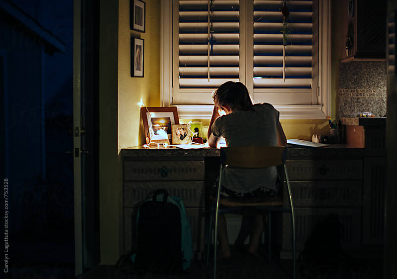 Teenage girl sitting at a desk in her home at night - frustrated and trying to finish homework by Carolyn Lagattuta for Stocksy United