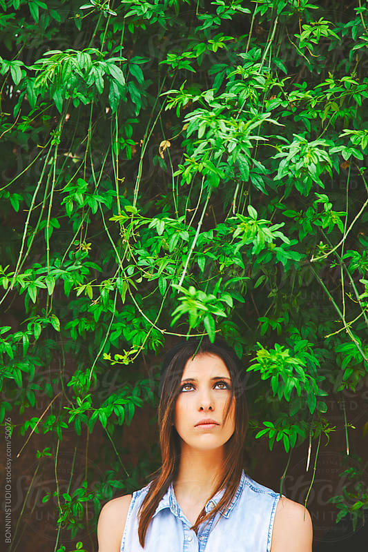 Young girl in front a wall covered of plants looking up by BONNINSTUDIO for Stocksy United