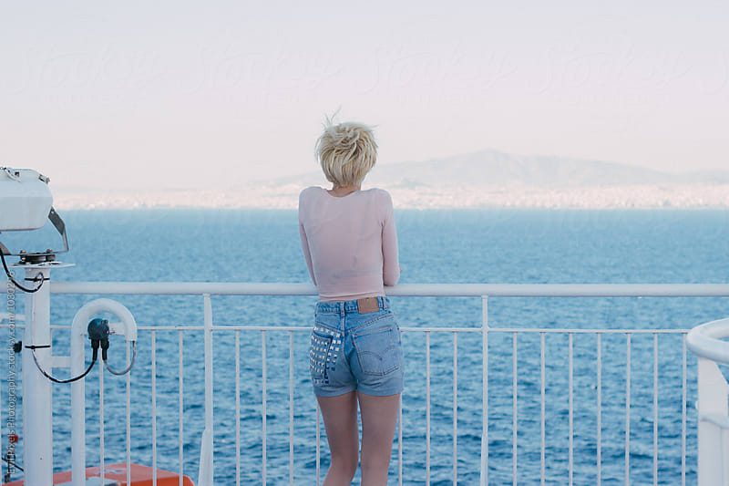 Portriat of a blonde short hair female model from back on ferry by Evil Pixels Photography for Stocksy United