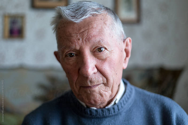 Portrait of a senior man sitting in the living room  by Jovana Milanko for Stocksy United