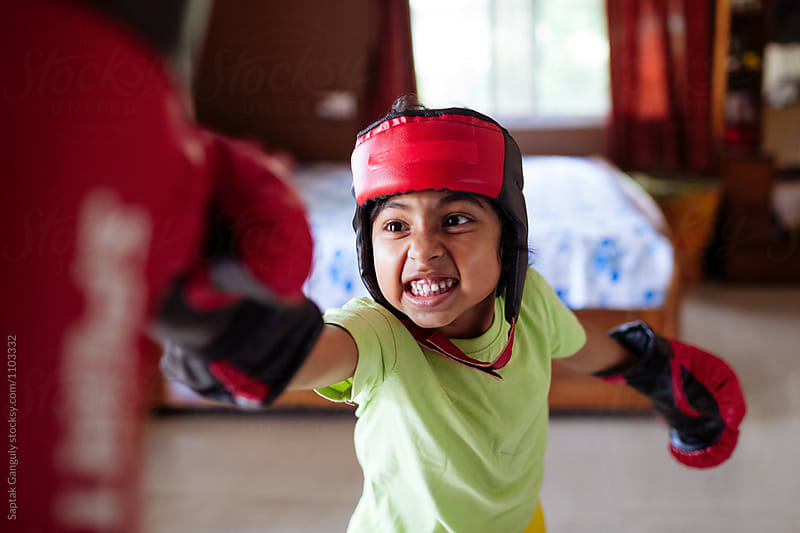 Child wearing boxing gloves punching punch bag by Saptak Ganguly for Stocksy United