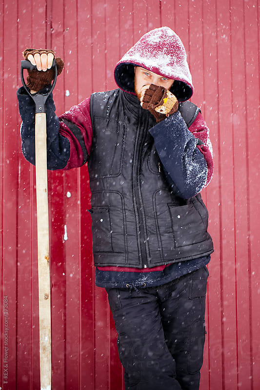 Young man in warm clothes standing outdoors with shovel by Danil Nevsky for Stocksy United