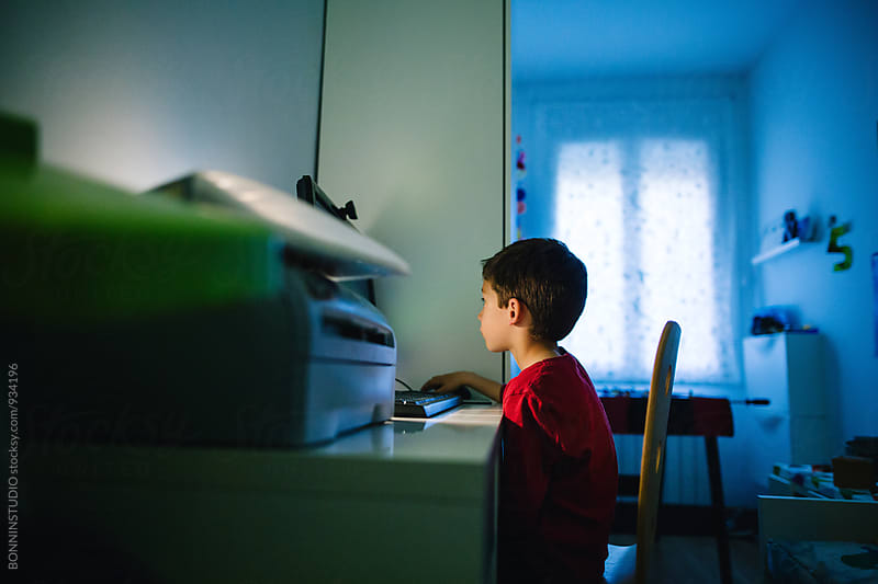 Side view of a little boy studying on computer at home. by BONNINSTUDIO for Stocksy United