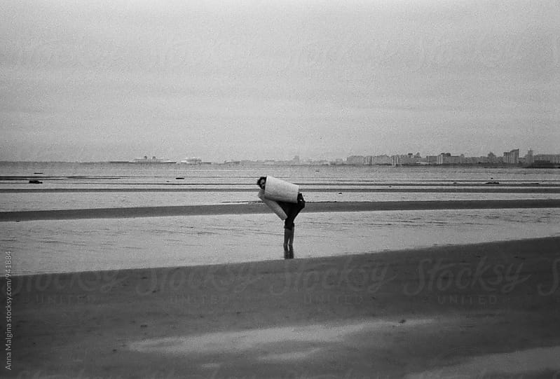 A black and white photo of man at the beach by Anna Malgina for Stocksy United