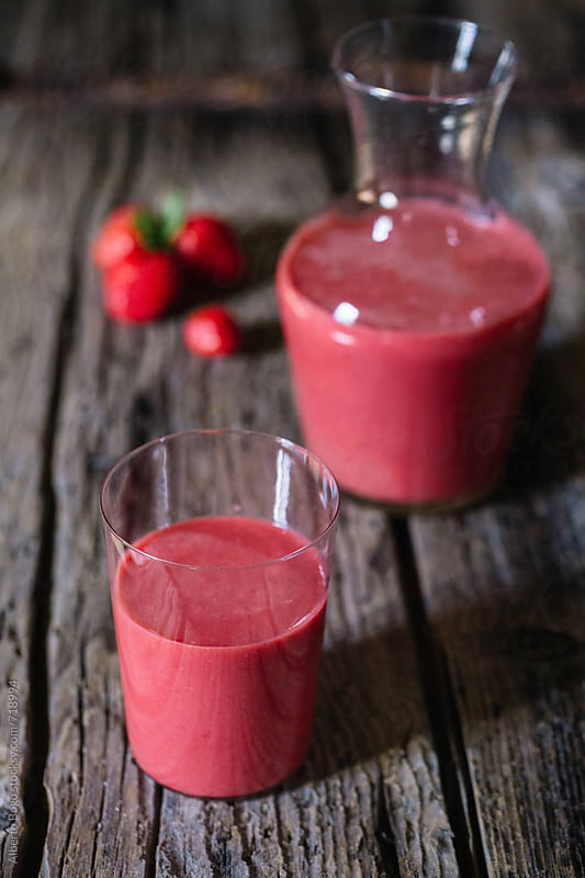 Red healthy strawberry smoothies on wooden table  by Alberto Bogo for Stocksy United