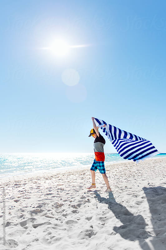 Boy flying a striped blue towel behind him at the beach on a sunny day by Angela Lumsden for Stocksy United