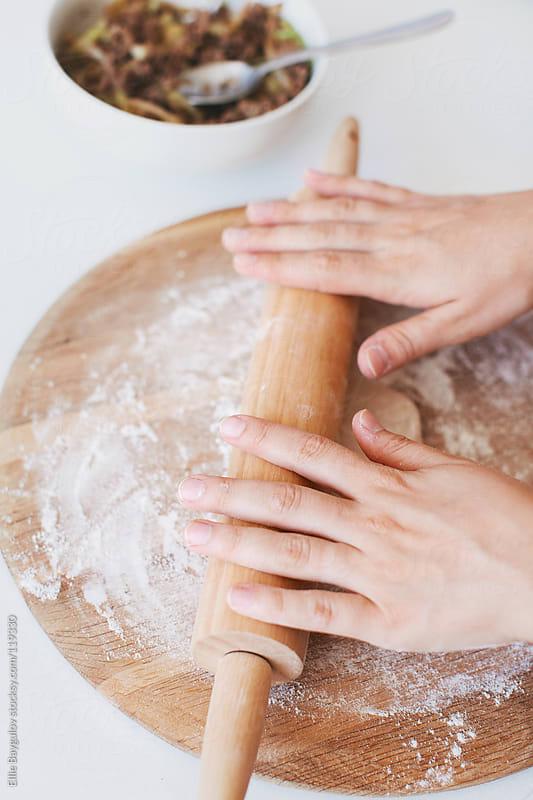 Woman rolling dough by Ellie Baygulov for Stocksy United