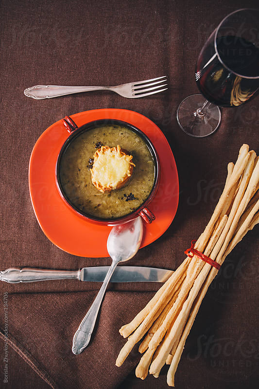 Onion soup in red bowl and baguettes with cheese on top by Borislav Zhuykov for Stocksy United