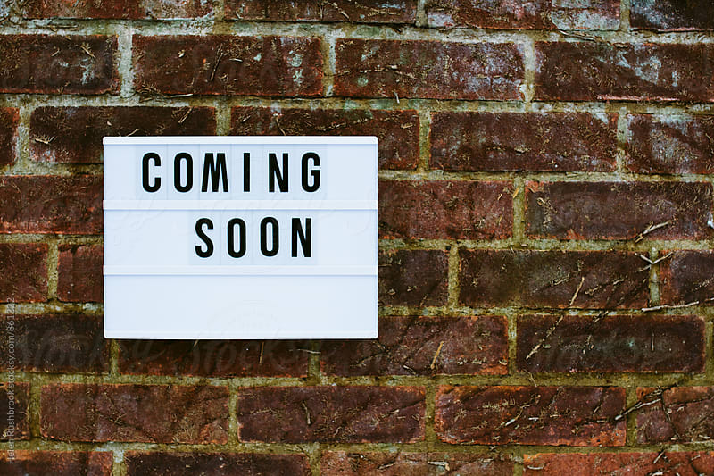 The words coming soon spelled out on a cinematic light-box on a brick wall by Helen Rushbrook for Stocksy United