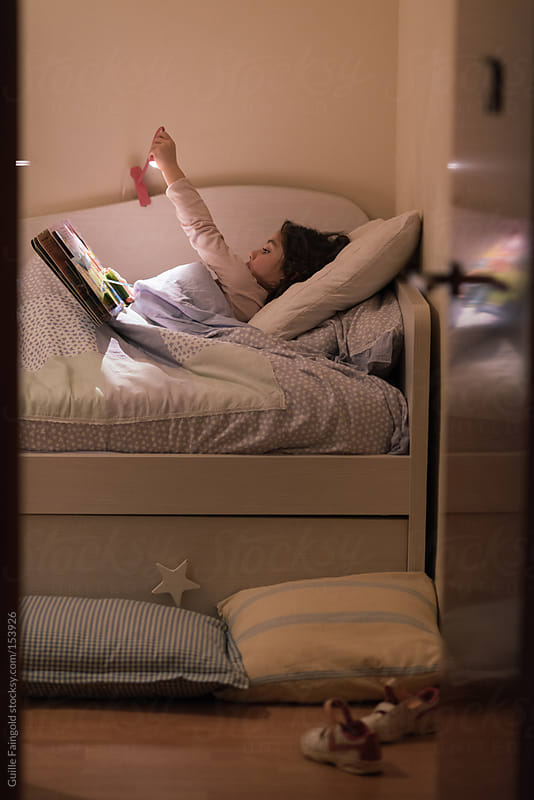 Little girl reading book in bed. by Guille Faingold for Stocksy United