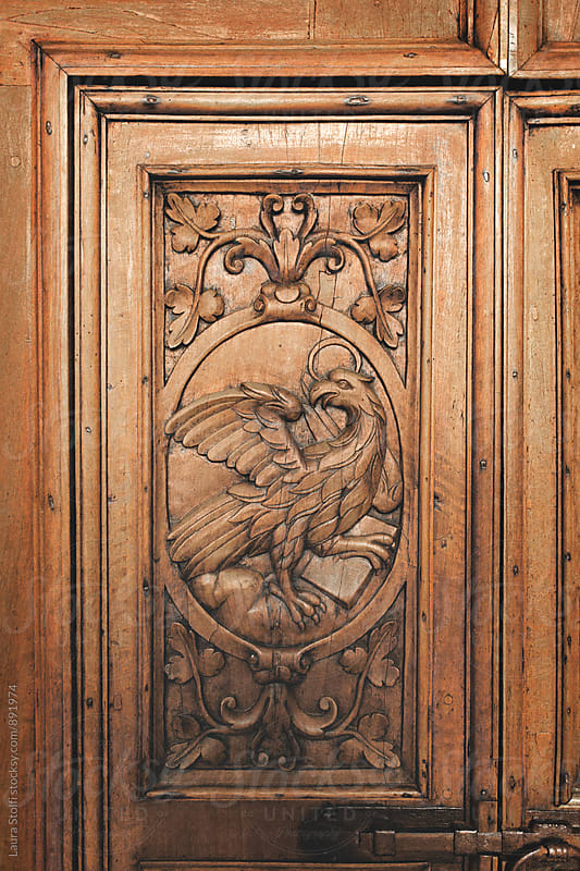 Eagle inlaid on ancient abbey's wooden portal symbolizing John evangelist by Laura Stolfi for Stocksy United