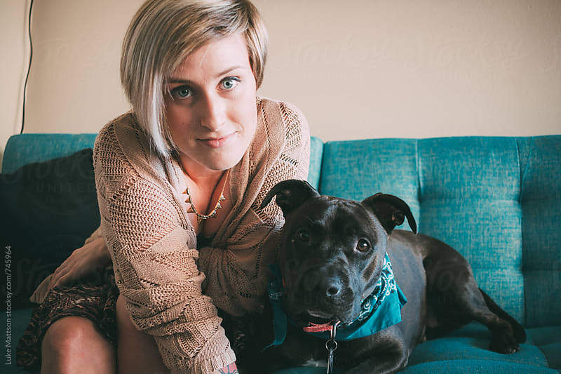 Young Blonde Tattooed Woman Sitting On Turquoise Couch With Pet Pit Bull by Luke Mattson for Stocksy United