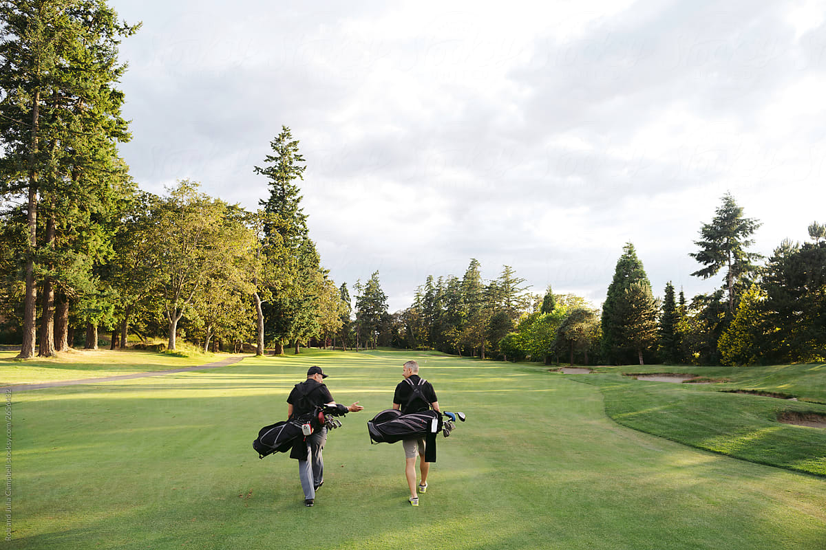 Two men walking on golf course. by Rob and Julia Campbell - Stocksy United