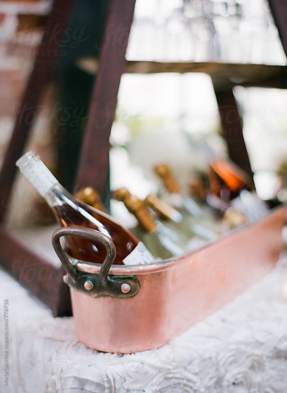 Wine bottles in a copper ice bucket by Marta Locklear for Stocksy United