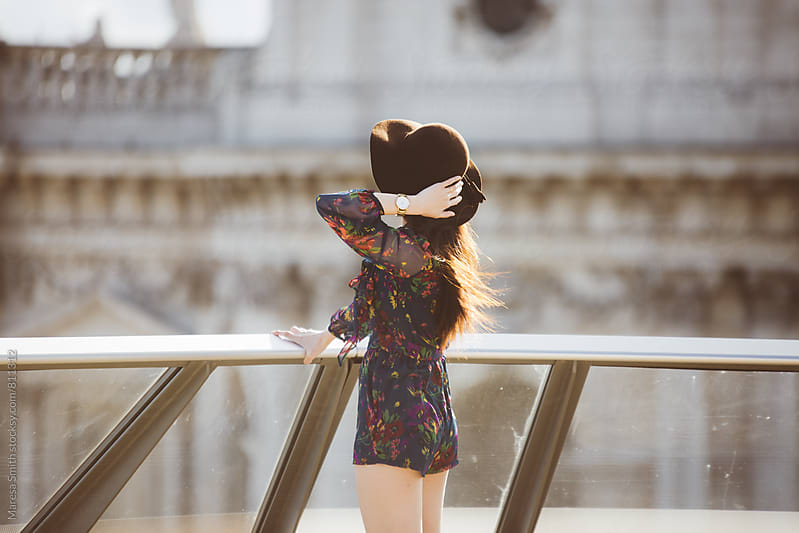 A brunette girl holds onto her hat as she looks at the view from a city balcony by Maresa Smith for Stocksy United