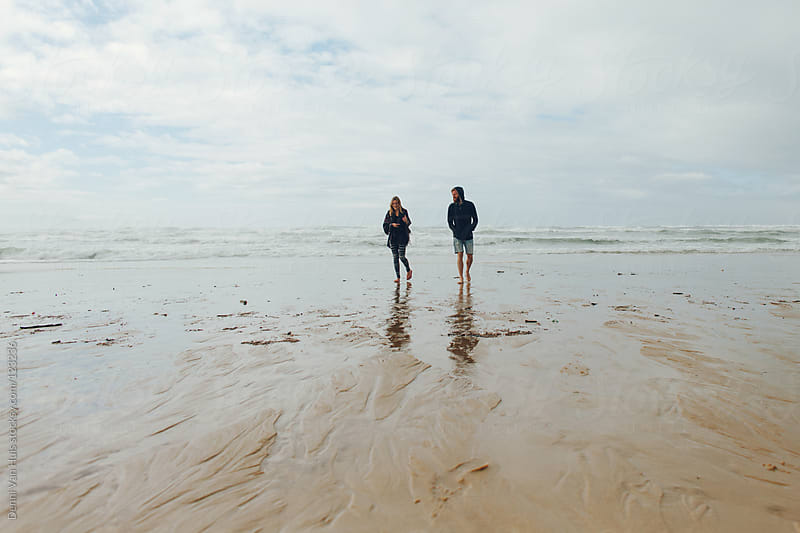 Friends walking on the beach. by Denni Van Huis for Stocksy United