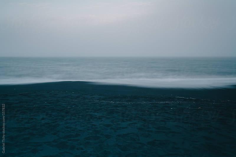 Black volcanic sand beach in Iceland by Gabriel Tichy for Stocksy United
