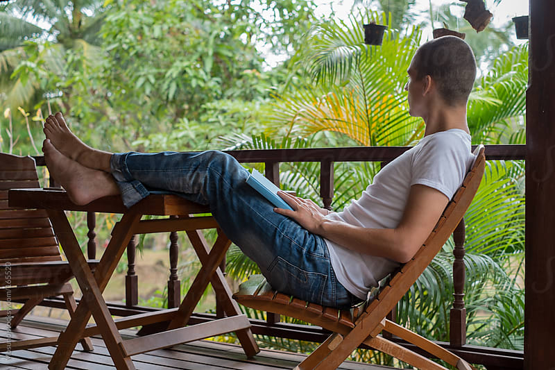 Man Relaxing on a Tropical Terrace  by Mosuno for Stocksy United