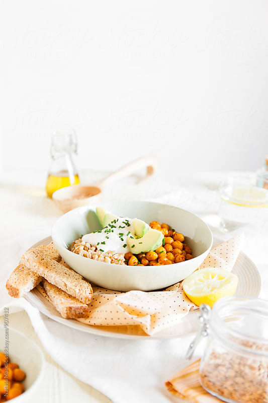 Spelt, chickpeas and avocado bowl with yogurt sauce by Nataša Mandić for Stocksy United
