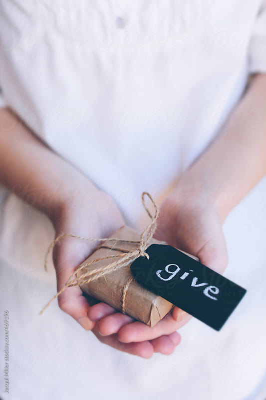 Girls hands holding a gift with the word 'give' written on a black slate tag by Jacqui Miller for Stocksy United