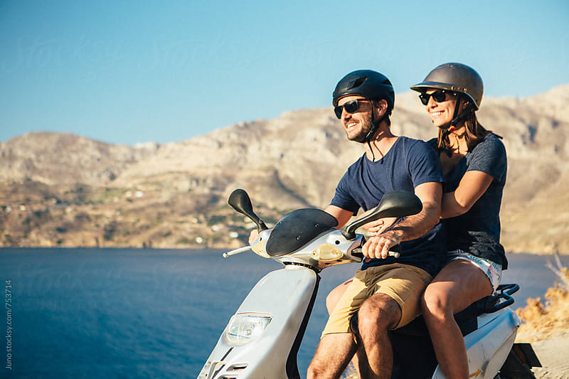 happy couple on a moped enjoying the view over the ocean in Kalymnos, Greece by Micky Wiswedel for Stocksy United