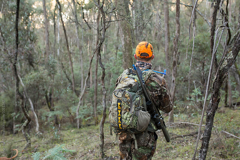 The back of a hunter, blending in to the bush by Reece McMillan for Stocksy United