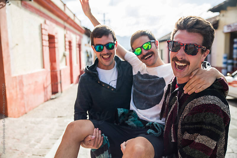 Three young friends wearing sunglasses having fun taking one in their linked arms like a chair in a traditional mexican village by Alejandro Moreno de Carlos for Stocksy United