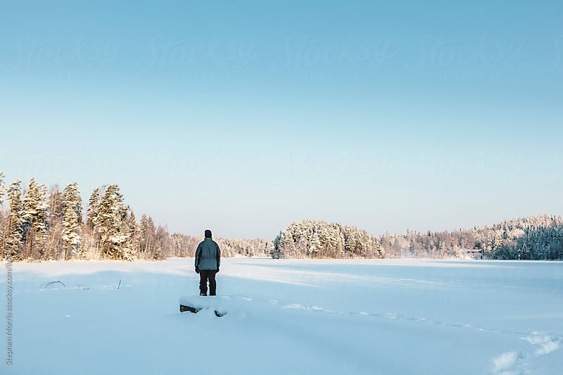 Lone Man Looking out on Winter Landscape by Stephen Morris for Stocksy United