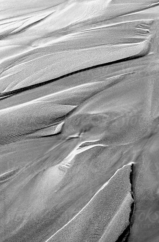 Closeup of sand patterns at receding tide black and white image by Ron Mellott for Stocksy United