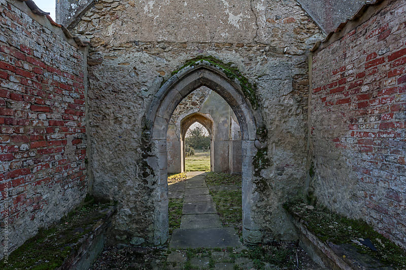 Arched entrance and exit to a derelict church by Paul Phillips for Stocksy United