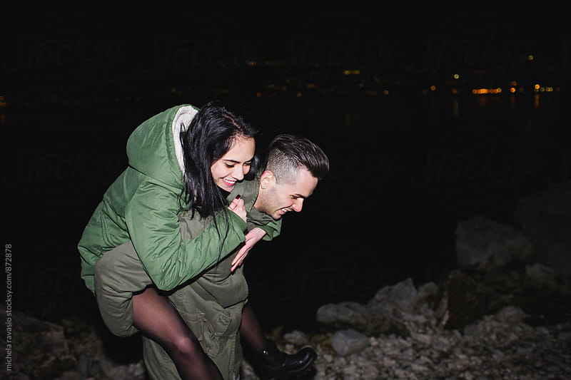 Young couple having fun at the lake at night by michela ravasio for Stocksy United