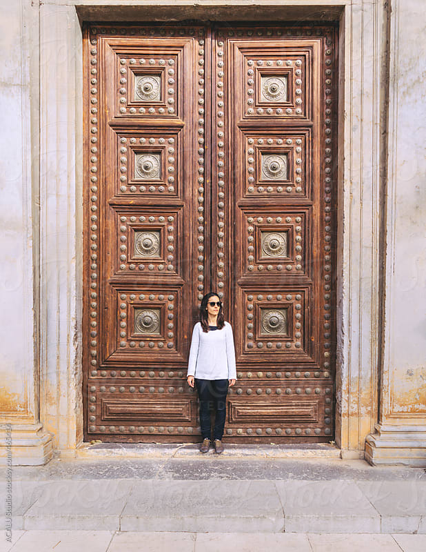 Woman in front of a large wooden door by ACALU Studio for Stocksy United