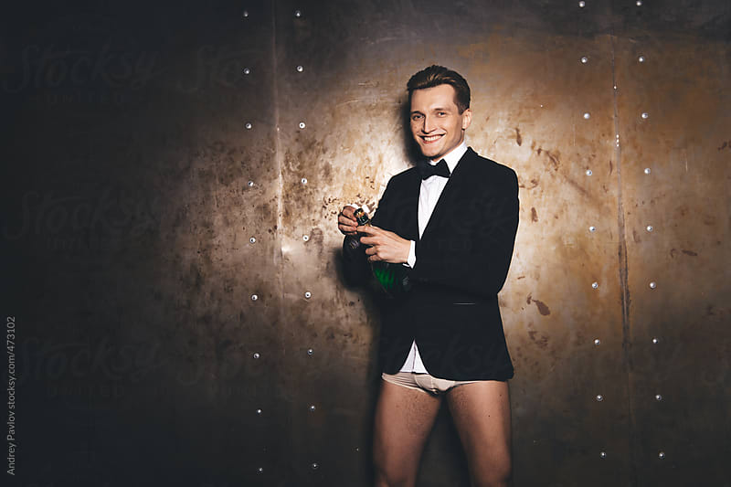 Men dressed in suit without pants opening champagne by Andrey Pavlov for Stocksy United