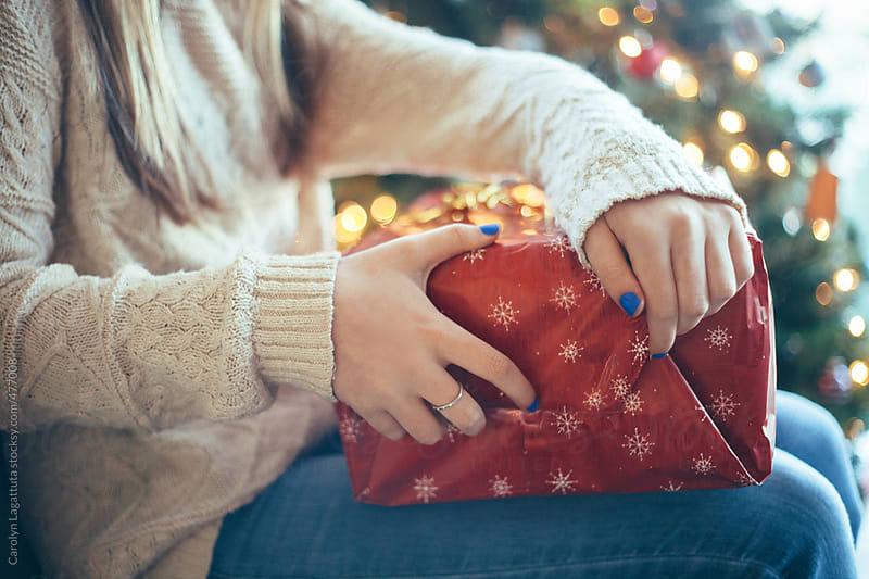 Teenage girl opening a Christmas present by Carolyn Lagattuta for Stocksy United