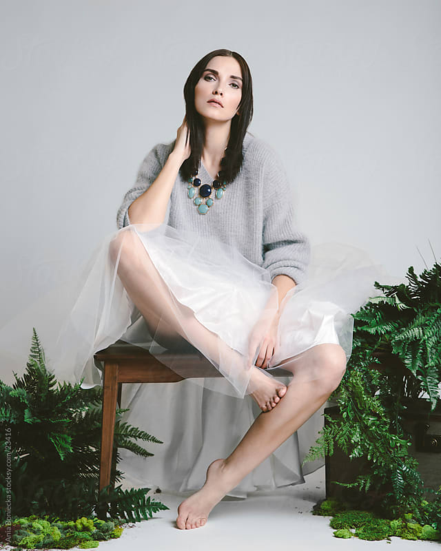 A beautiful brunetter wearing a sweater and a white toulle skirt by Ania Boniecka for Stocksy United