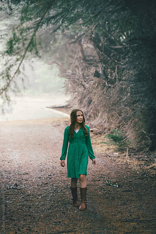 girl in green dress walking up a driveway in the woods by Gillian Vann for Stocksy United