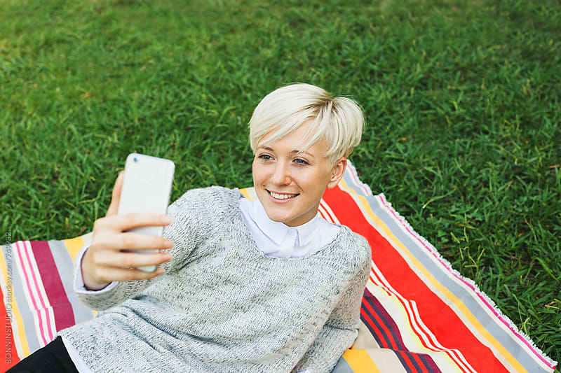 Smiling blonde woman taking a selfie. by BONNINSTUDIO for Stocksy United
