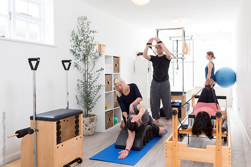 Pilates studio with three students and a trainer  by Paul Phillips for Stocksy United