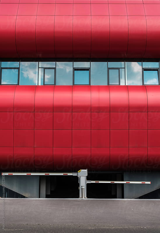 Red modern building with garage entrance  in front of it by Marko Milanovic for Stocksy United