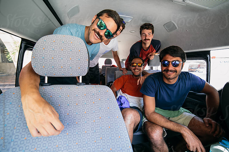 Four young men friends with funky sunglasses in a minivan ready for a road trip during their vacation travel by Alejandro Moreno de Carlos for Stocksy United