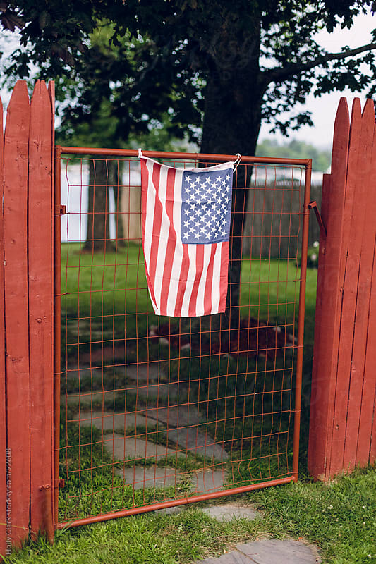 An American flag hangs an old gate near a lake.  by Holly Clark for Stocksy United
