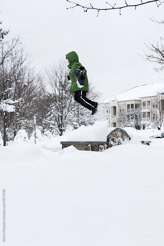 Child jumping in snow after snowstorm by Kerry Murphy for Stocksy United